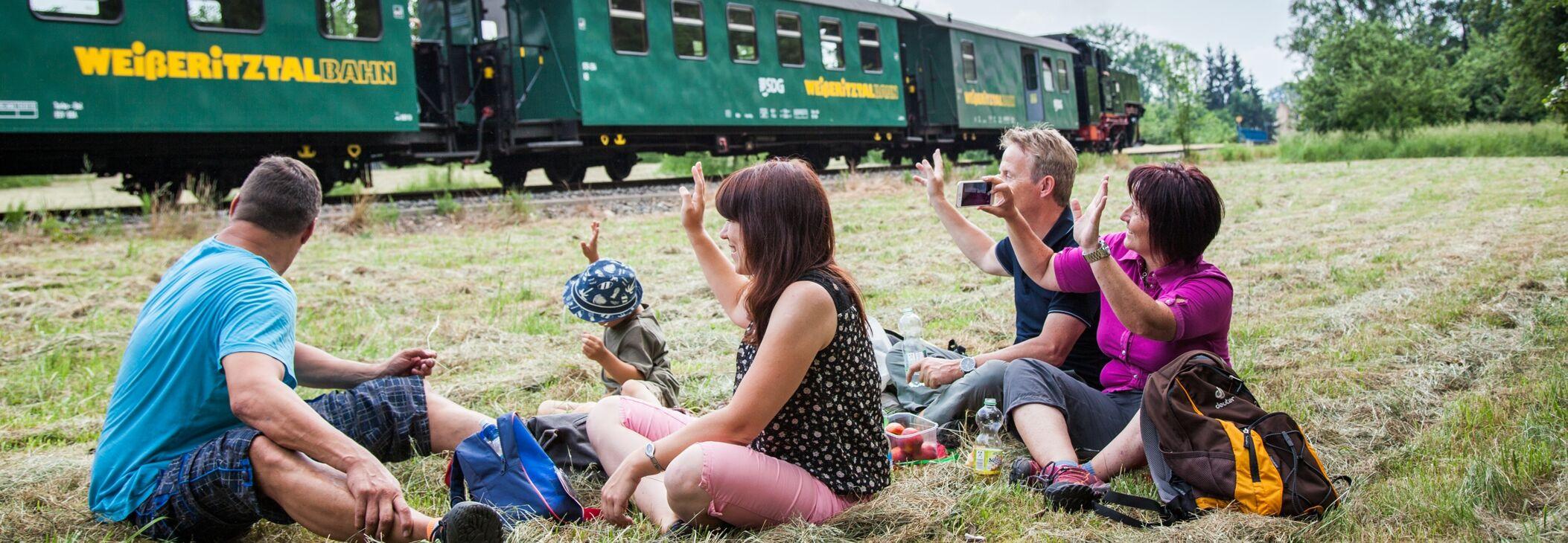 Familie macht Picknick mit Blick auf den Dampfzug