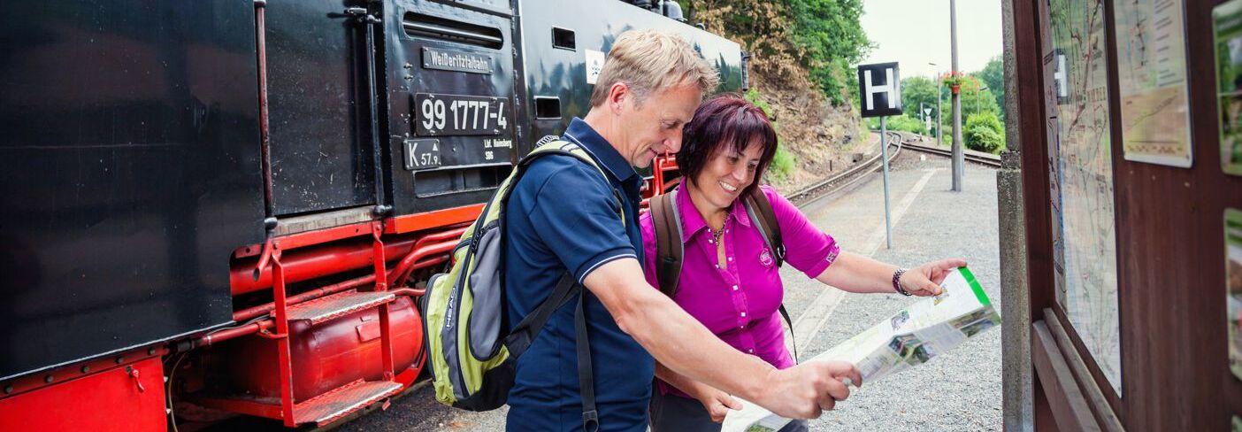 Paar informiert sich mit Wanderkarte der Weißeritztalbahn