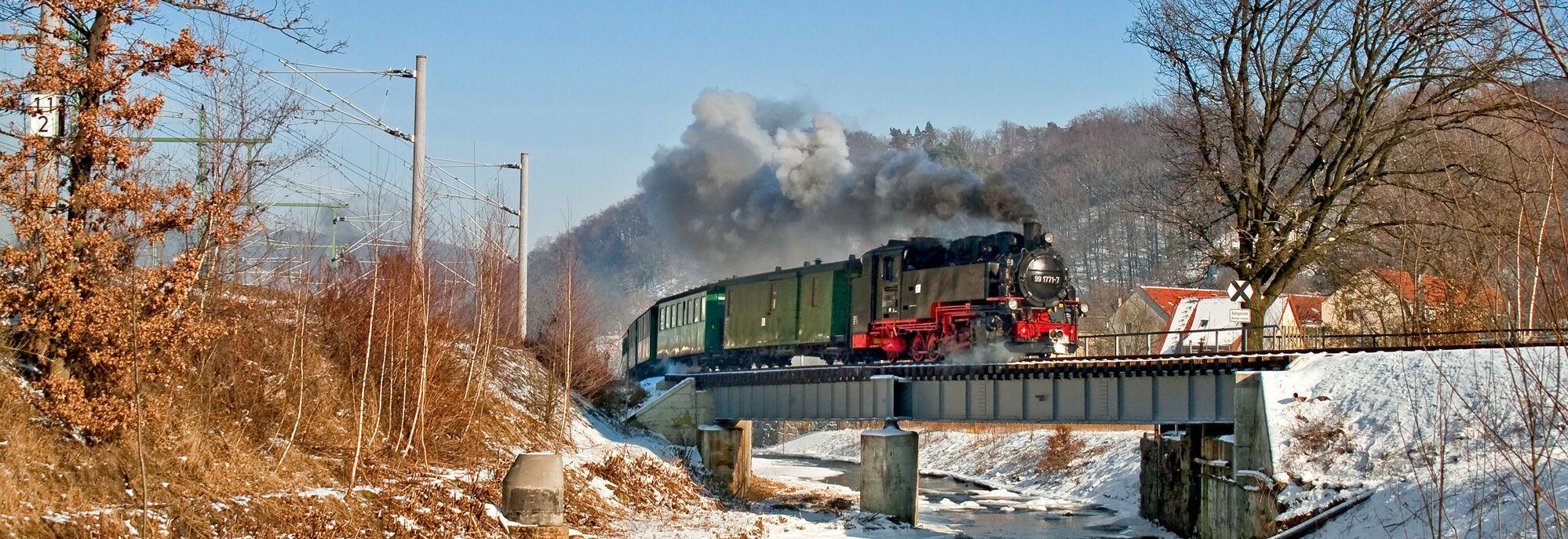 Zug dampft im Winter auf einer Brücke über den Fluss